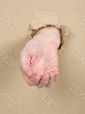 Male hand through in cardboard