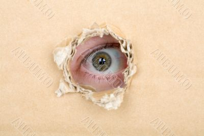 Eye looking from a hole in a cardboard