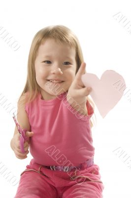 pretty small girl is cutting paper heart shape