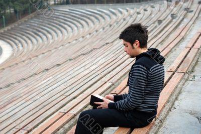 lonely man reading book in empty stadium
