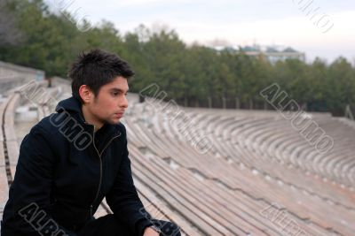cool man sitting in stadium grandstands