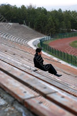 man sitting alone at stadium tribun