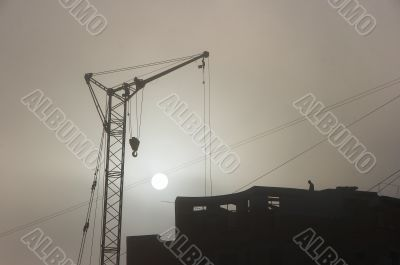 Gray sunset sky with lifting construction cranes