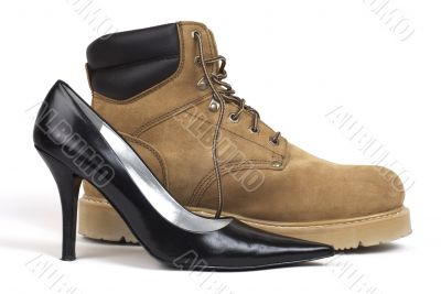 Side Shot of Black Women`s High-Heel Shoe Beside Workboot