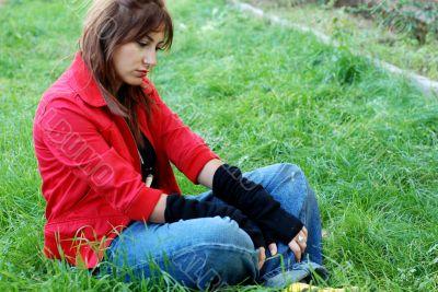 young woman sitting on grass, sad expression