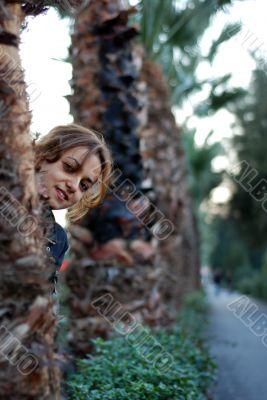 beautiful woman hiding between the trees