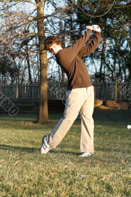 Youth golfer hitting iron