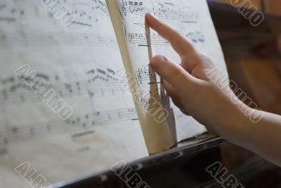 finger at music sheet