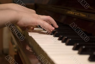 child`s hands on the piano roll