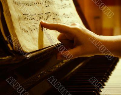 child finger at music sheet