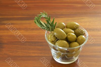 Single jar of green olives with rosemary