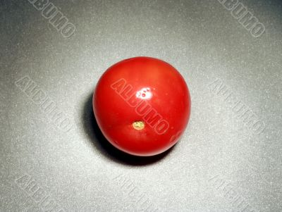 A single tomato on the table surface