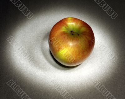 A red apple in the light circle