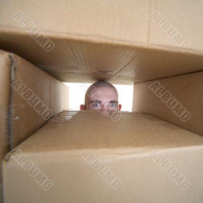 Face looking trough window in pile cardboards