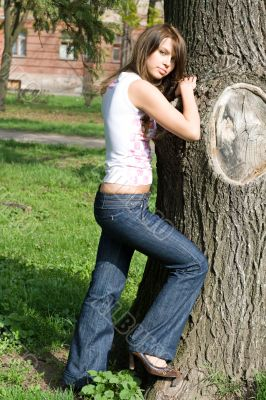 The beauty girl standing near a tree