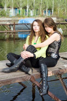 Two beautiful embracing girls on a mooring