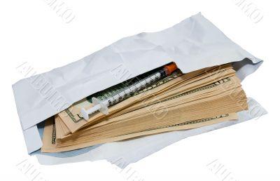 Dollars and syringe in open envelope