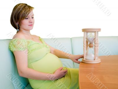 Pregnant woman looking on the hourglass