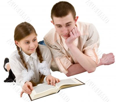 Girl and young man reading book in a reclining position