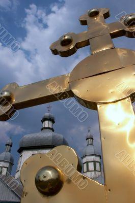 Huge golden christian cross near church