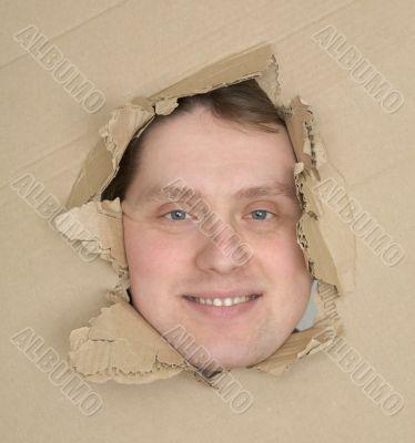 Male face look up through hole carton