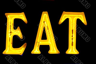 Neon sign with the word `Eat` over black