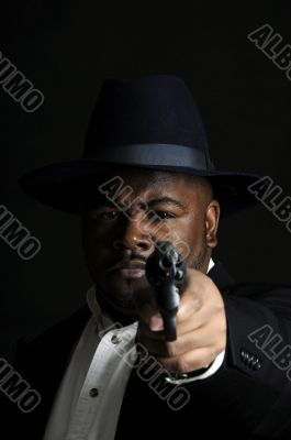 young African American man with gun pointed