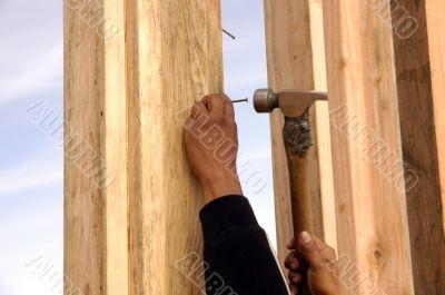 Hispanic carpenter pounding a nail