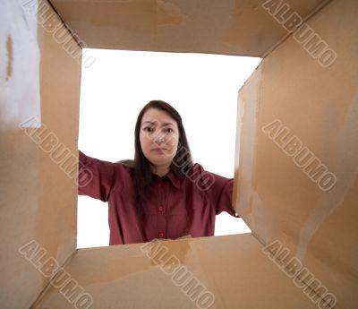 Female face into cardboard box