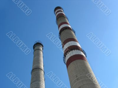 Two industrial chimneys with no smoke over blue sky