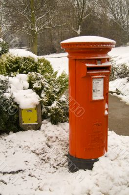 Traditional red British Post box in the snow