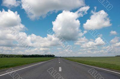 countryside asphalt road under cloudy blue sky