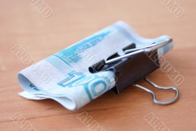 Clip with banknote on the wooden table