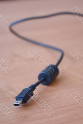 Black USB cable on wood background