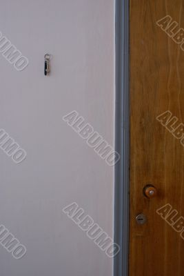 Wooden door and grey wall with a key