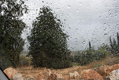 Rainy landscape in car window