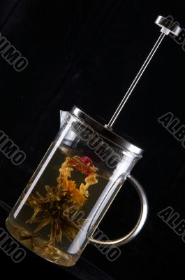 French-press with tea in black background