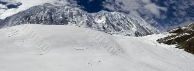 The picturesque mountain view with clouds, stones, peak and snow