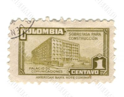 Old green stamp from Colombia with building