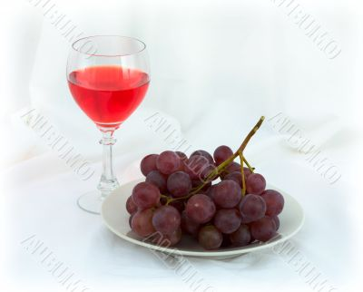 Still-life with a glass of red wine and grapes