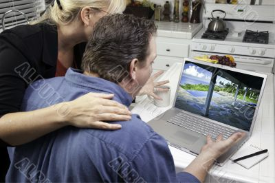 Couple In Kitchen Using Laptop - Real Estate and Vacations