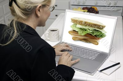Woman In Kitchen Using Laptop - Food and Recipes