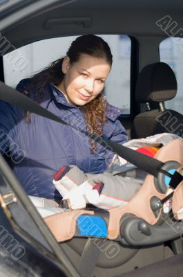 Mother fastens a children`s safety seat