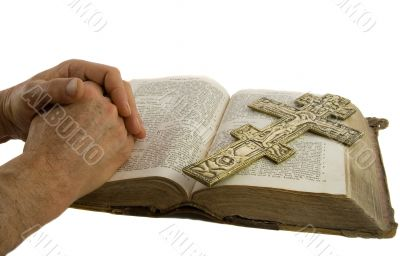 Hands closed in prayer and cross on an open bible
