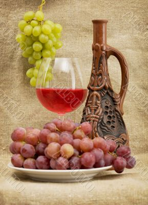 Ceramic bottle, grapes and red wine