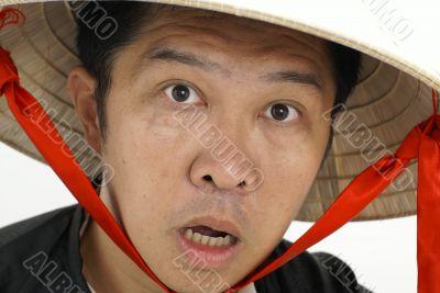 Surprised asian man wearing hat