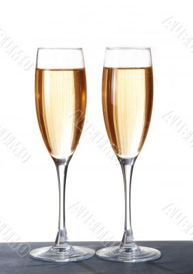 Two elegant champagne glasses on a dark surface