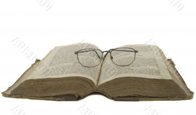 Vintage open book bible open and glasses on it isolated over whi