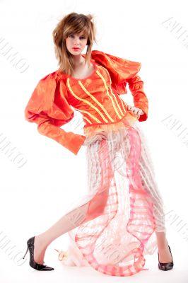Cute teenage girl in an orange fancy dress posing