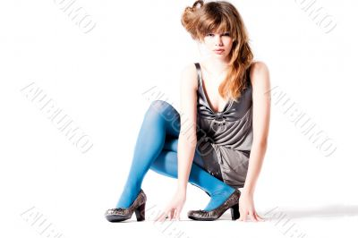 Teenager in blue pantyhose and grey blouse sitting concentrated